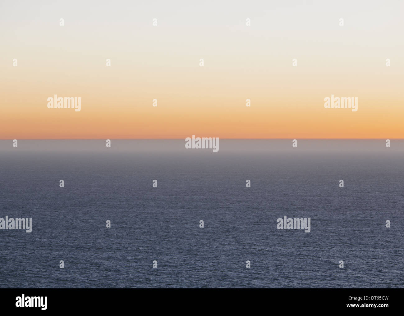A view over the Pacific Ocean and the sunset on the horizon. - Stock Image