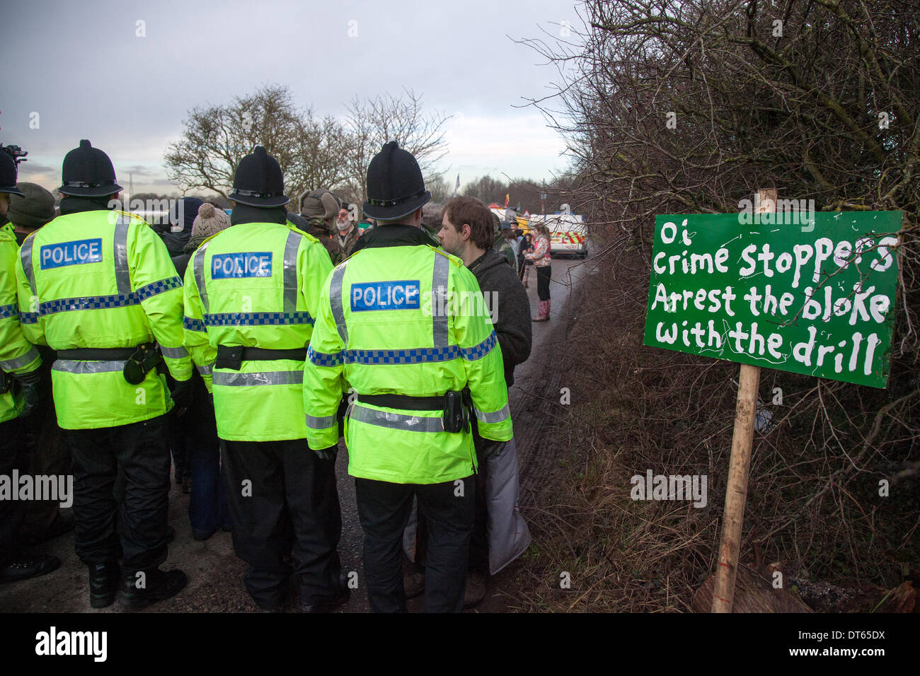 Officers in hi-vis jackets policing Barton Moss exploration site in Manchester, UK. 10th Feb, 2014. Crime Stoppers arrest the bloke with the drill' Protests by anti-fracking campaigners and a policing operation by Greater Manchester Police continue at IGAS Drilling Site at Barton Moss. Protestors are seeking to delay and obstruct delivery vehicles and drilling equipment en-route to the controversial gas exploration site. Fracking protestors have set up a camp at Barton Moss Road, Eccles a potential methane-gas extraction site in Salford, Greater Manchester. - Stock Image