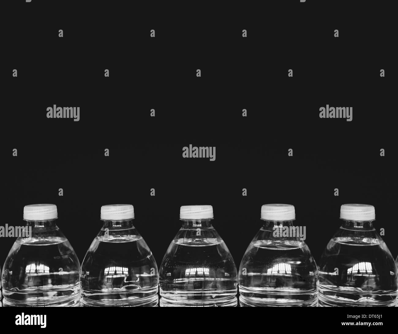 Row of clear, plastic water bottles filled with filtered water - Stock Image