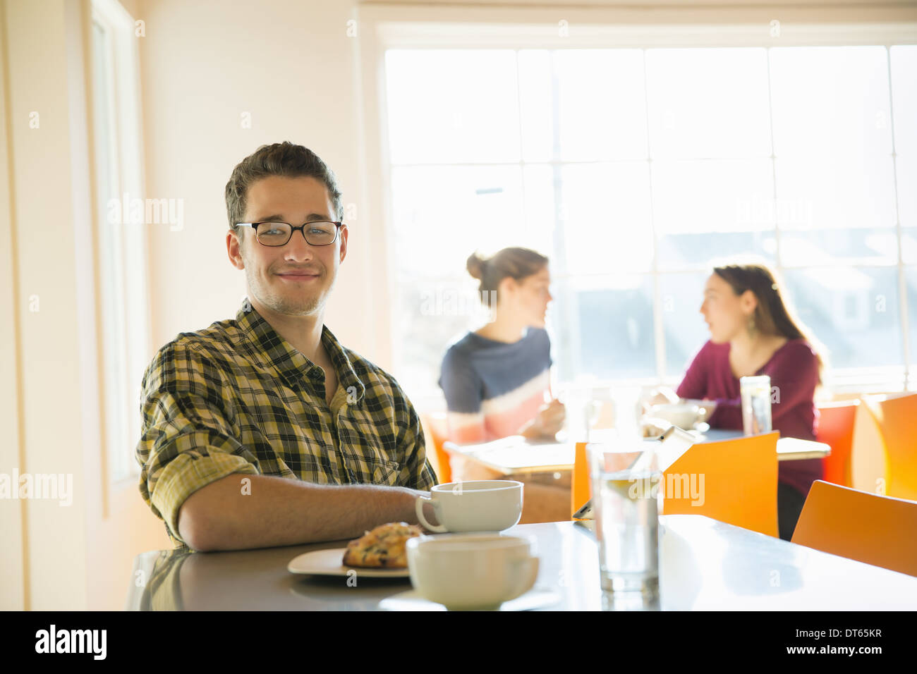A young man sitting at a coffee shop counter, with two women in the background. Stock Photo