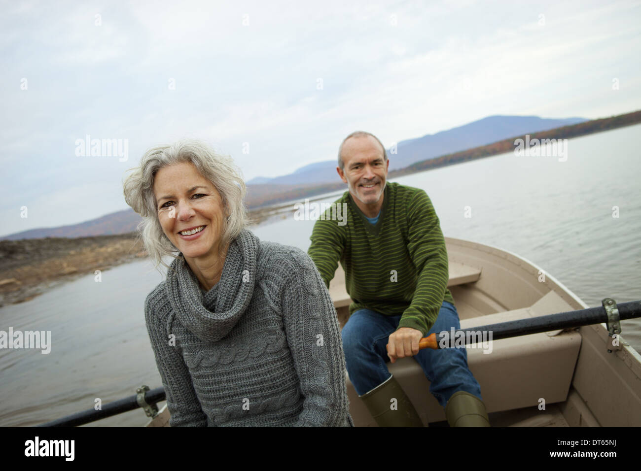 A couple, man and woman sitting in a rowing boat on the water on an autumn day. - Stock Image