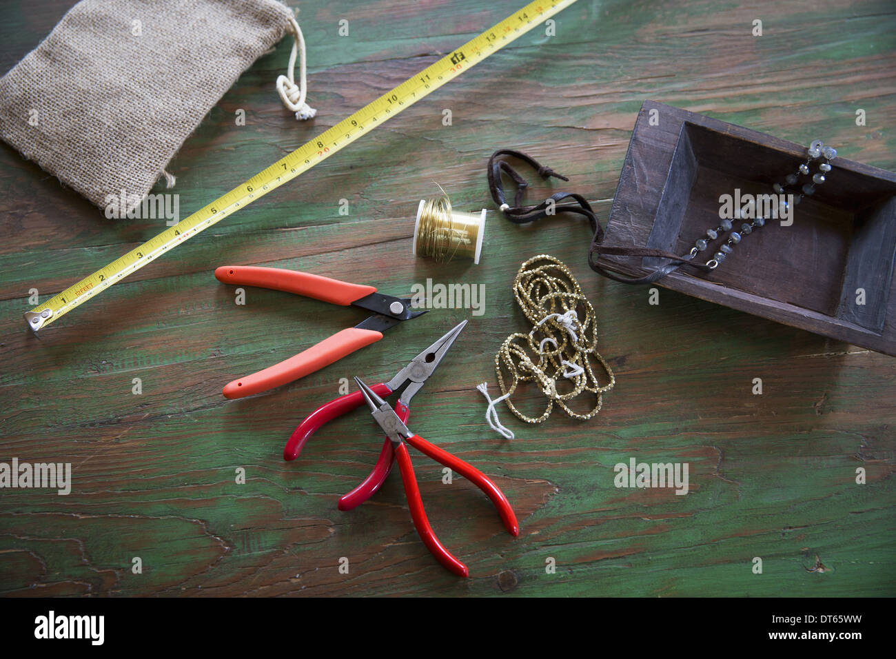 A tabletop with jewellery making equipment. Pliers, thread and a wooden tray, with measuring tape. - Stock Image