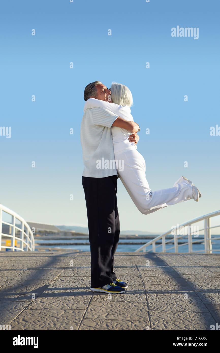 Man lifting woman up - Stock Image