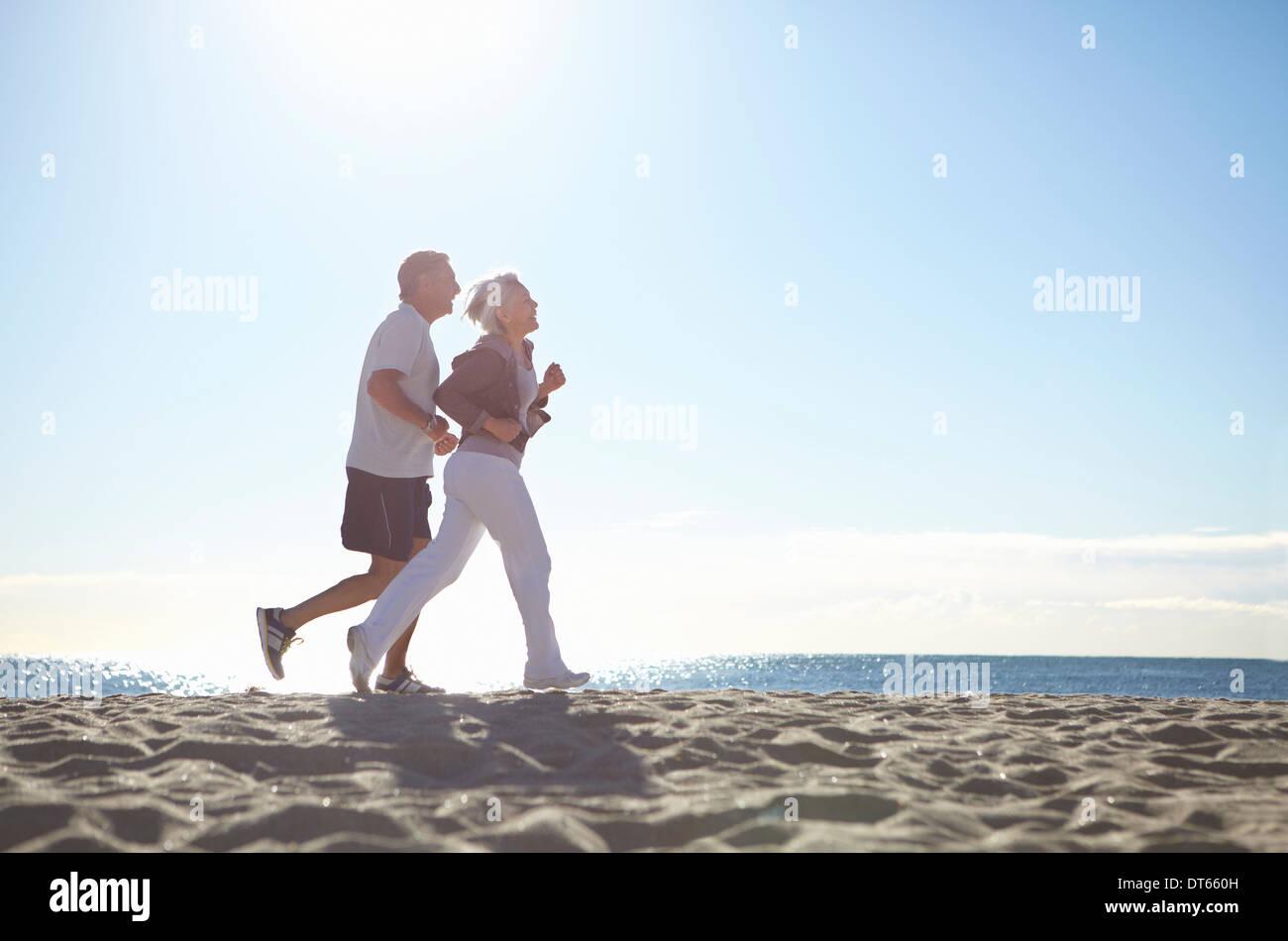 Couple jogging on beach - Stock Image