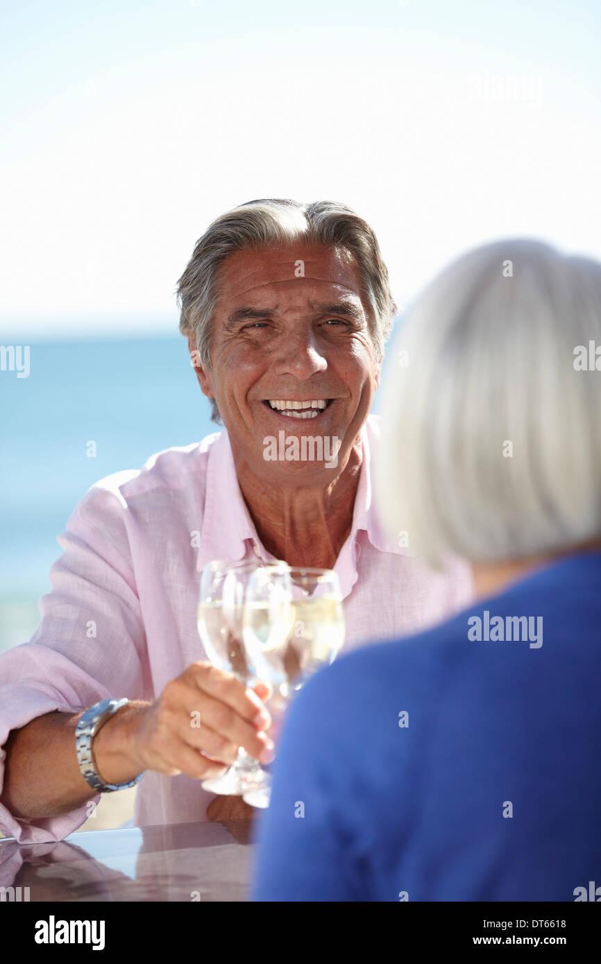 Couple enjoying wine by seaside Stock Photo