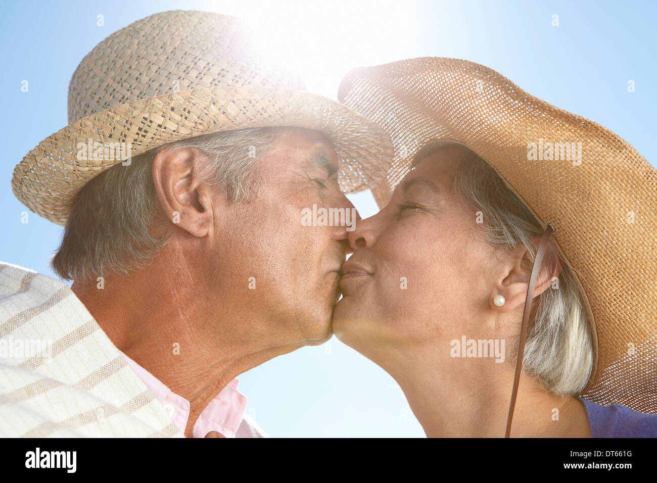 Couple wearing straw hats kissing - Stock Image