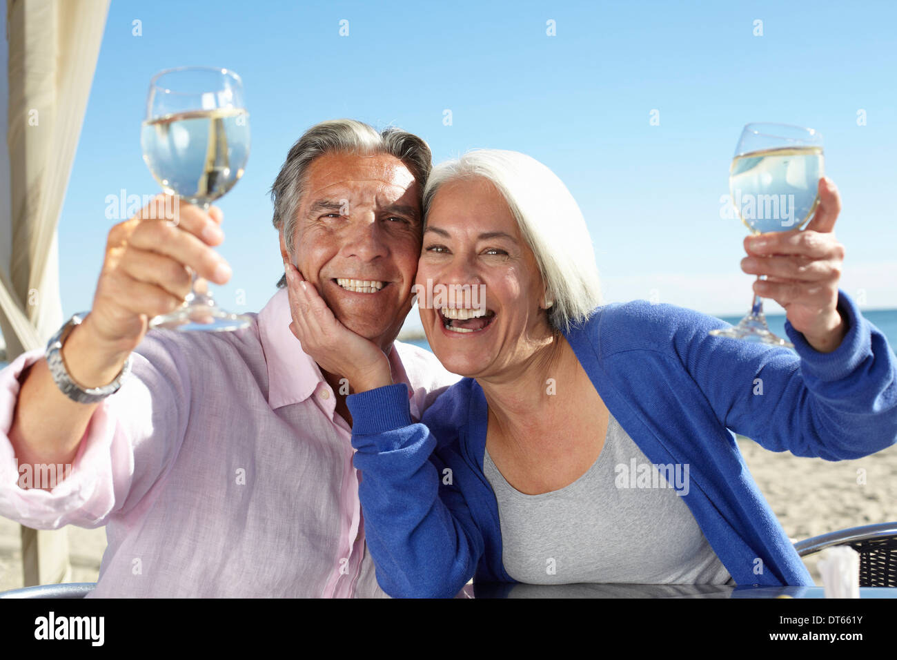 Couple enjoying wine by seaside Stock Photo