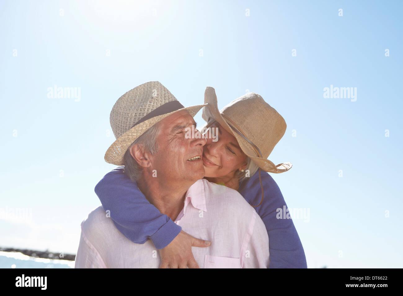 Couple wearing straw hats on beach - Stock Image