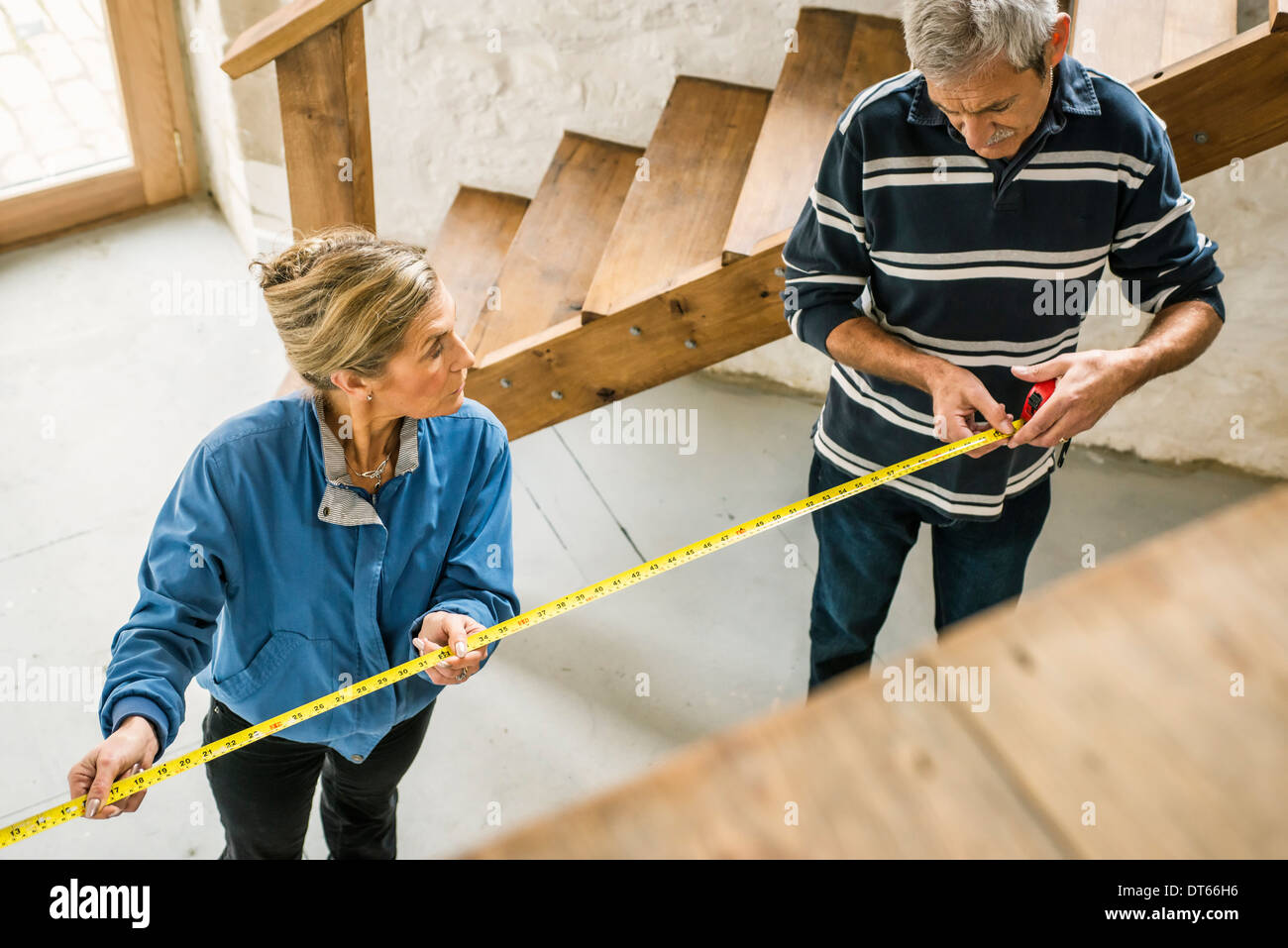 Senior couple doing DIY, using measuring tape - Stock Image