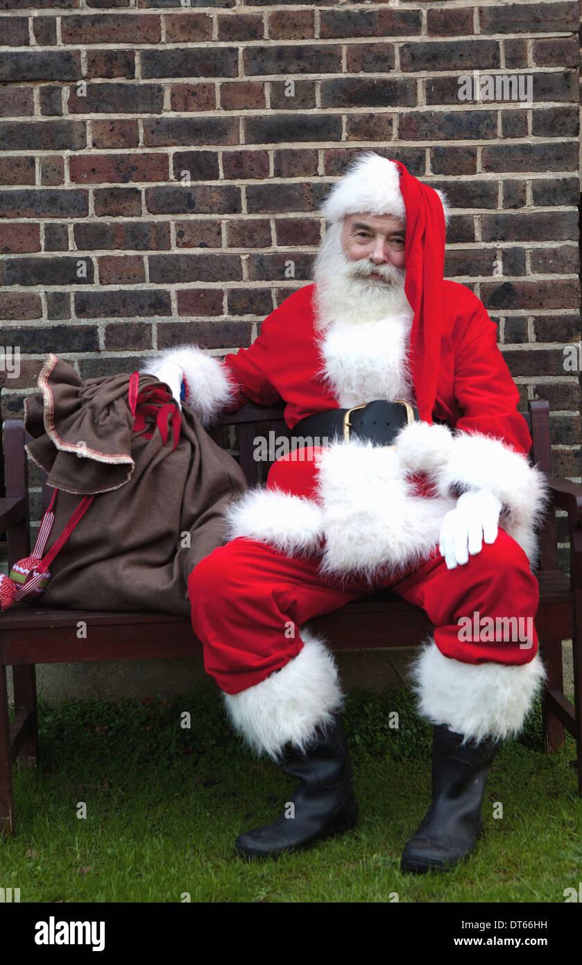 Santa Claus taking break on bench - Stock Image