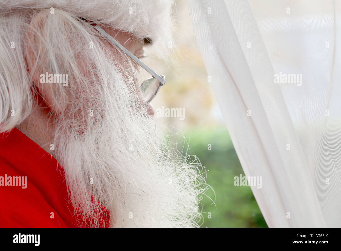 Santa Claus looking out of window - Stock Image