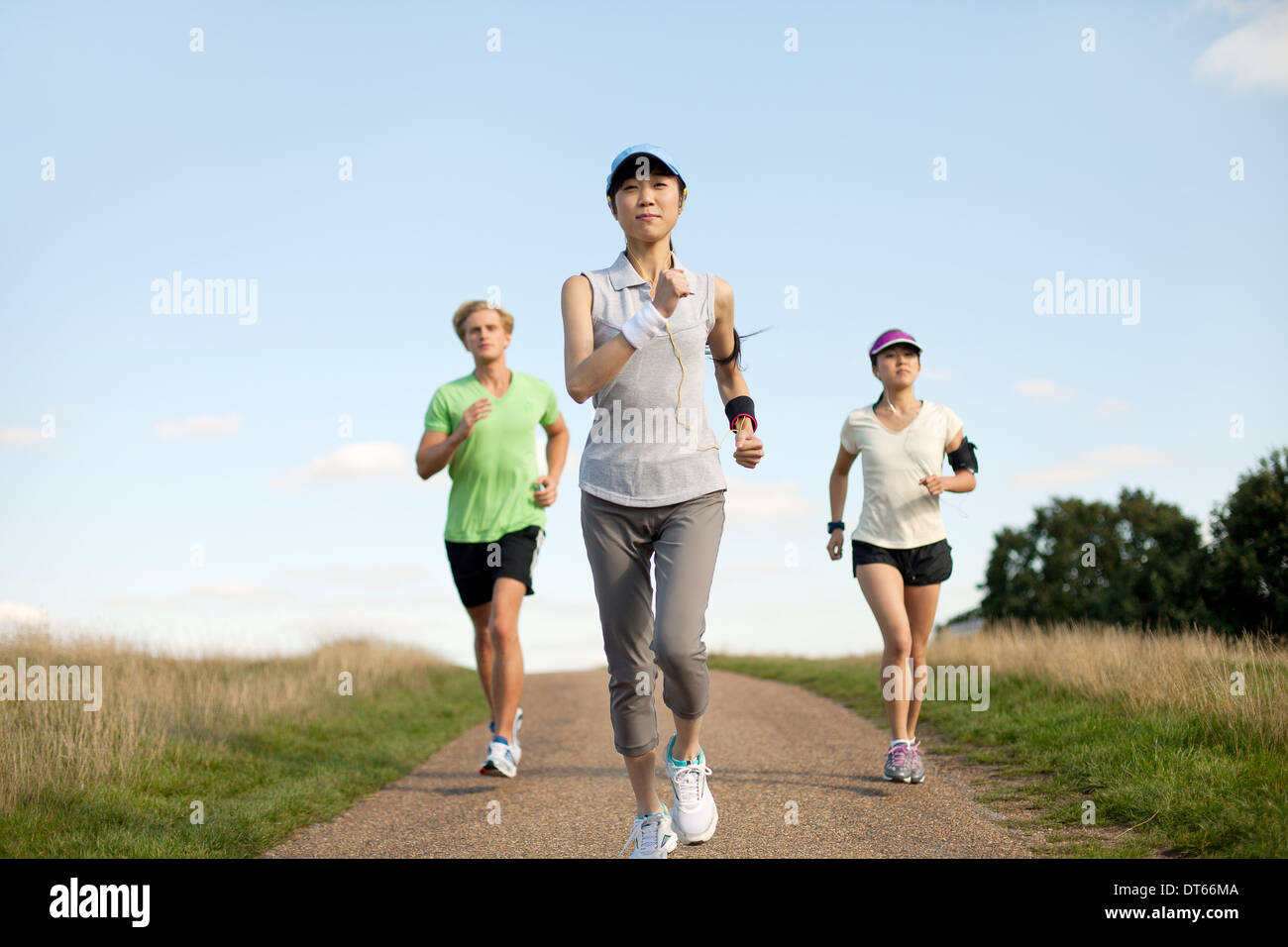 Three young adults jogging along field track Stock Photo