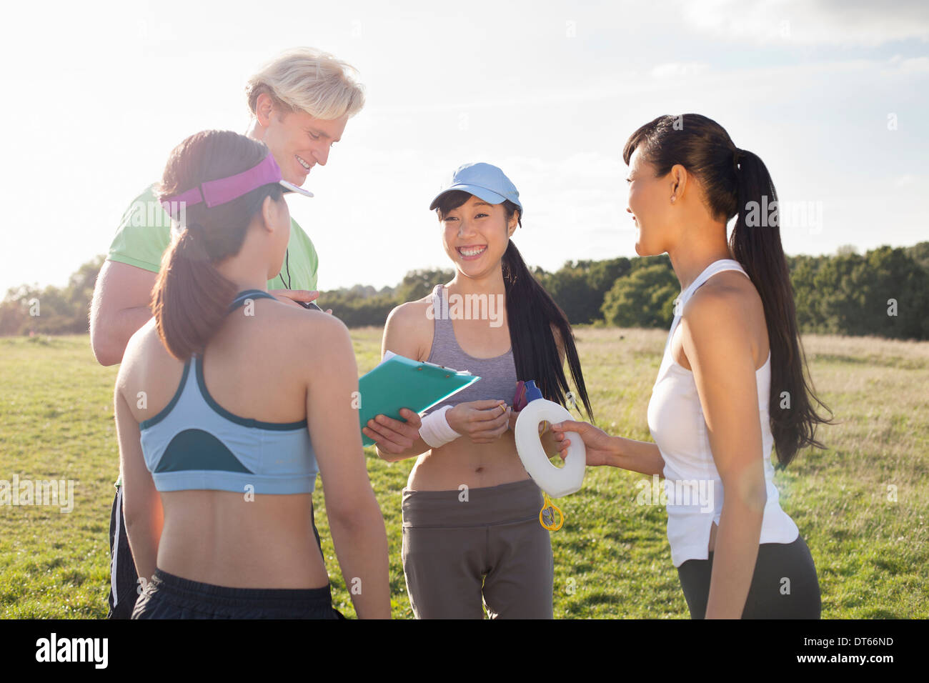 Personal trainer giving instruction to group of clients - Stock Image