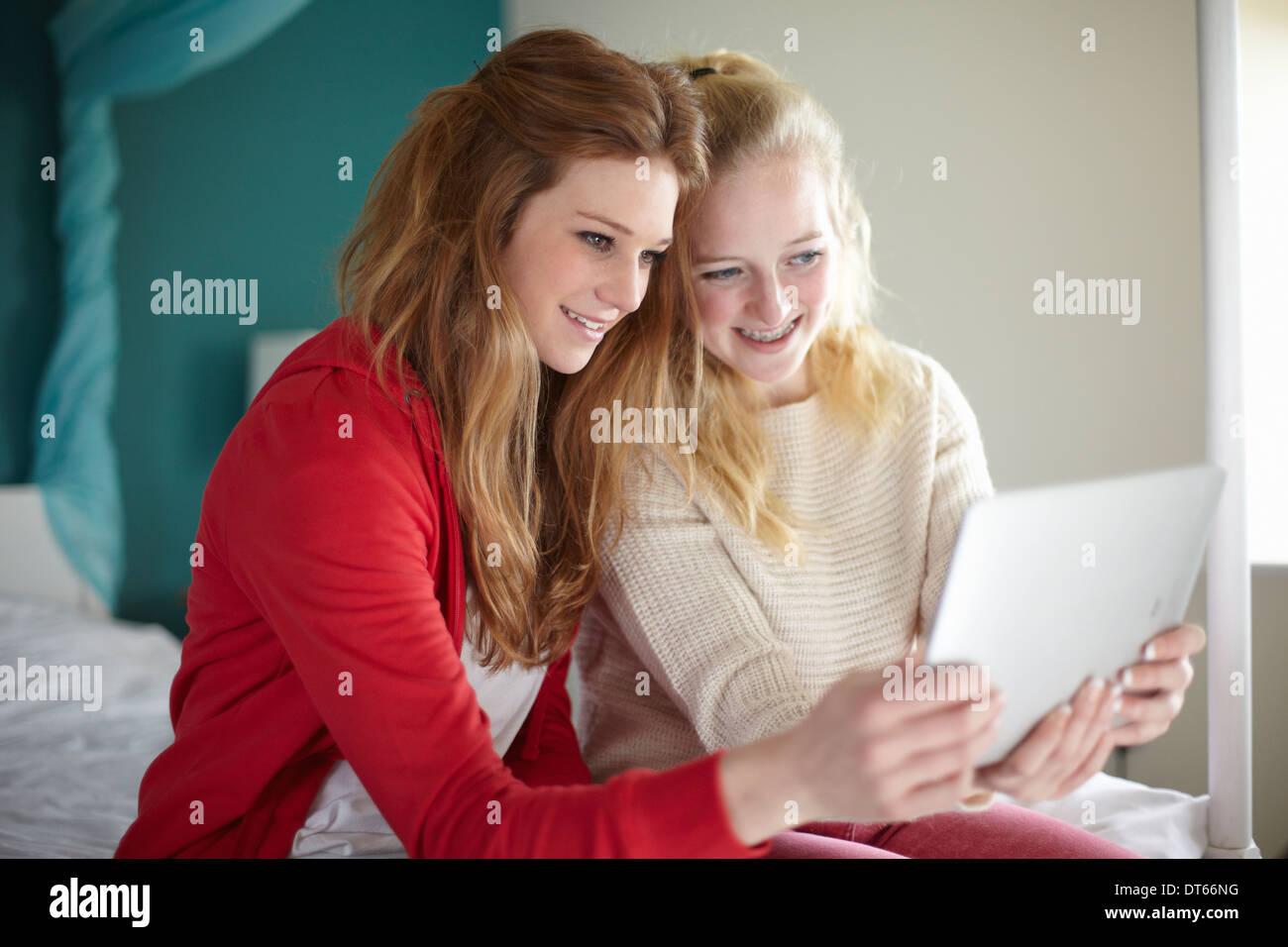 Two teenage girls looking at digital tablet in bedroom - Stock Image