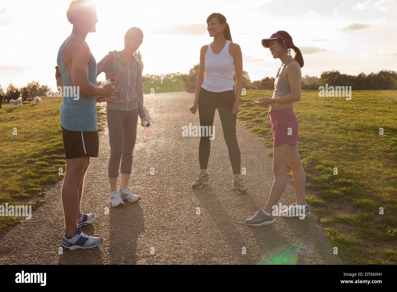 Personal trainer with group of clients preparing for run - Stock Image