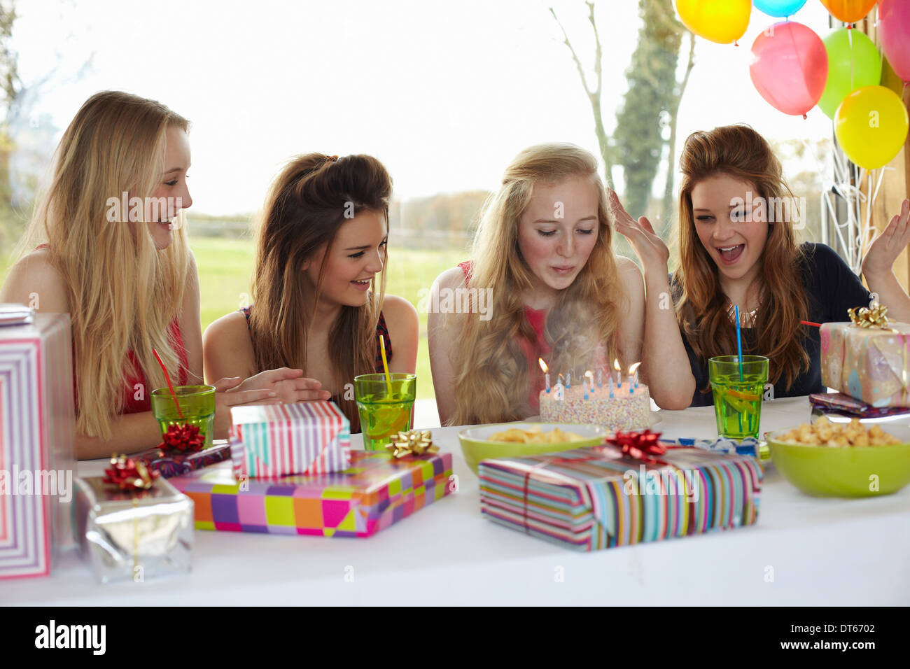 Teenage girl blowing out birthday candles with friends - Stock Image