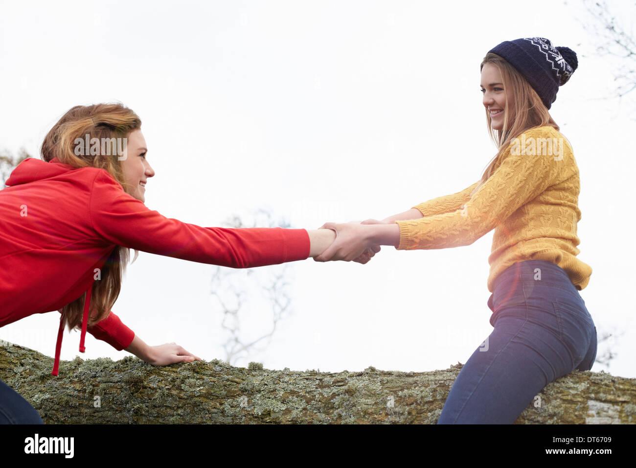 Teenage girls play fighting on tree trunk - Stock Image