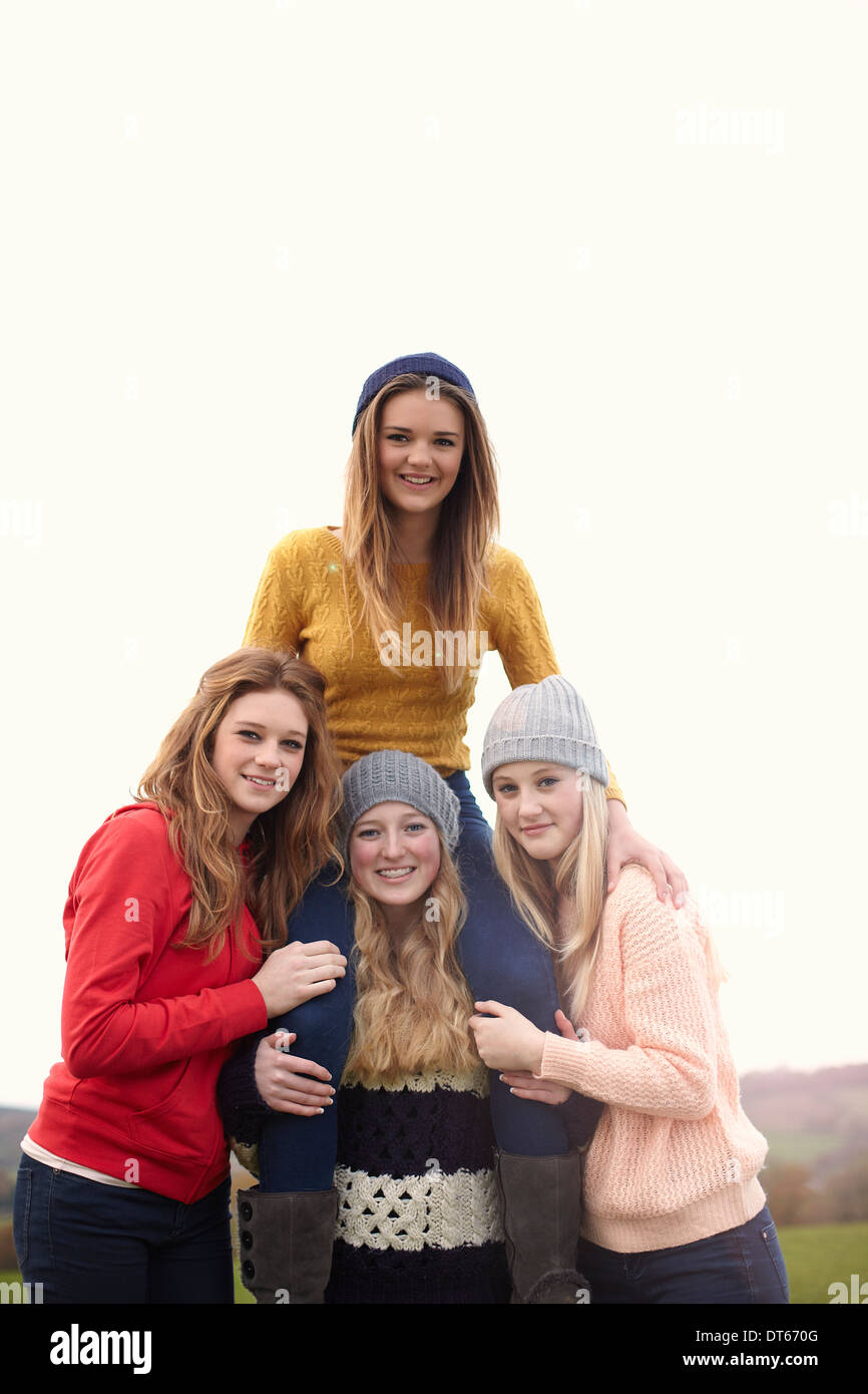 Teenage girl getting shoulder ride from friends - Stock Image