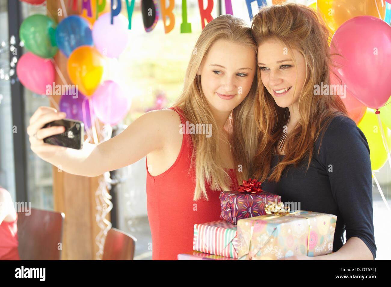 Two teenage girls taking selfie at birthday party - Stock Image