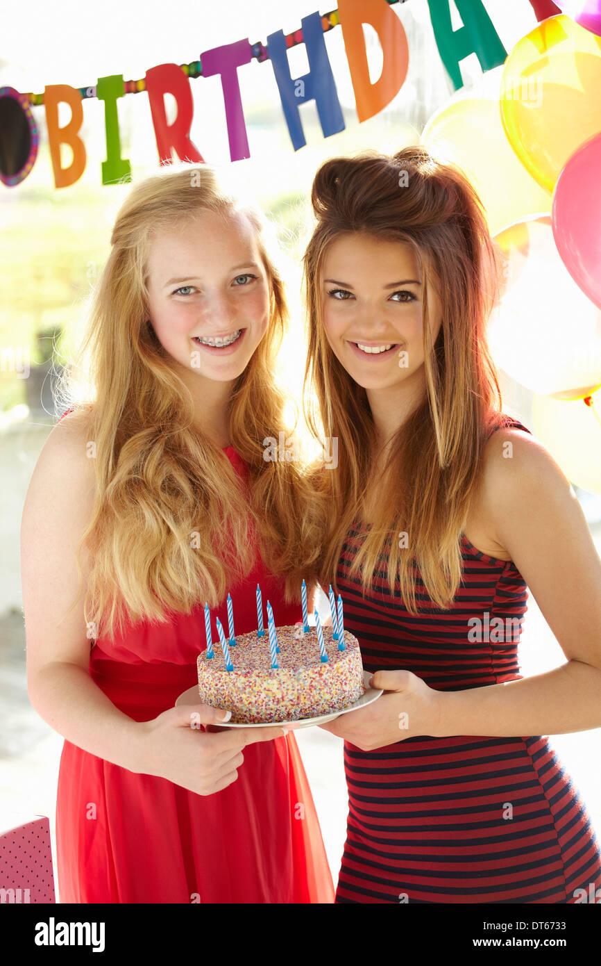 Two teenage girls holding birthday cake - Stock Image