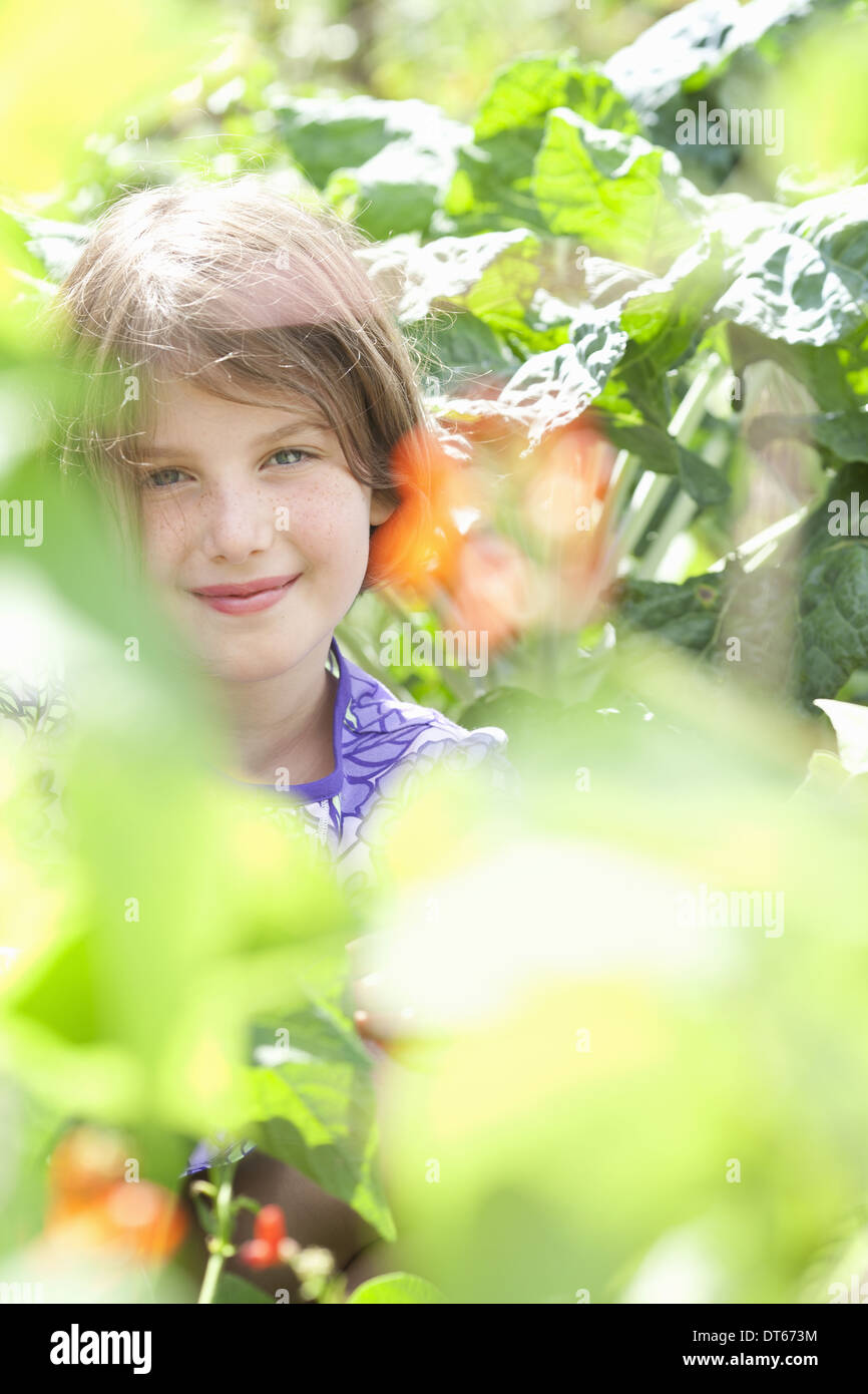 A young girl sitting in among the fresh green foliage of a garden. Vegetables and flowers. Picking fresh vegetables. - Stock Image