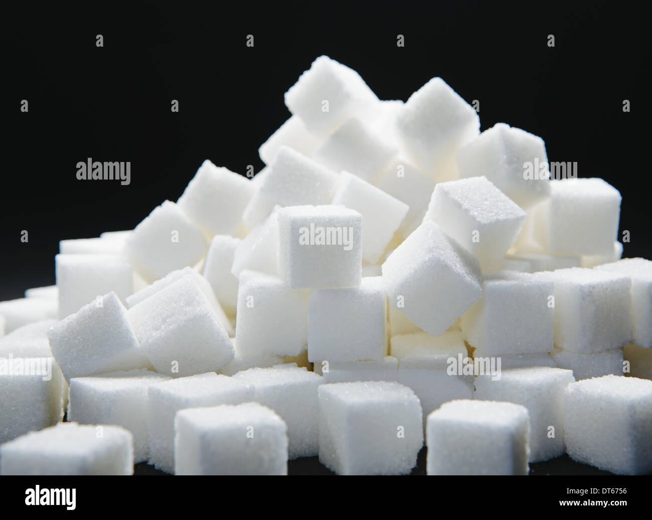 Pile of sugar cubes, black backdrop - Stock Image