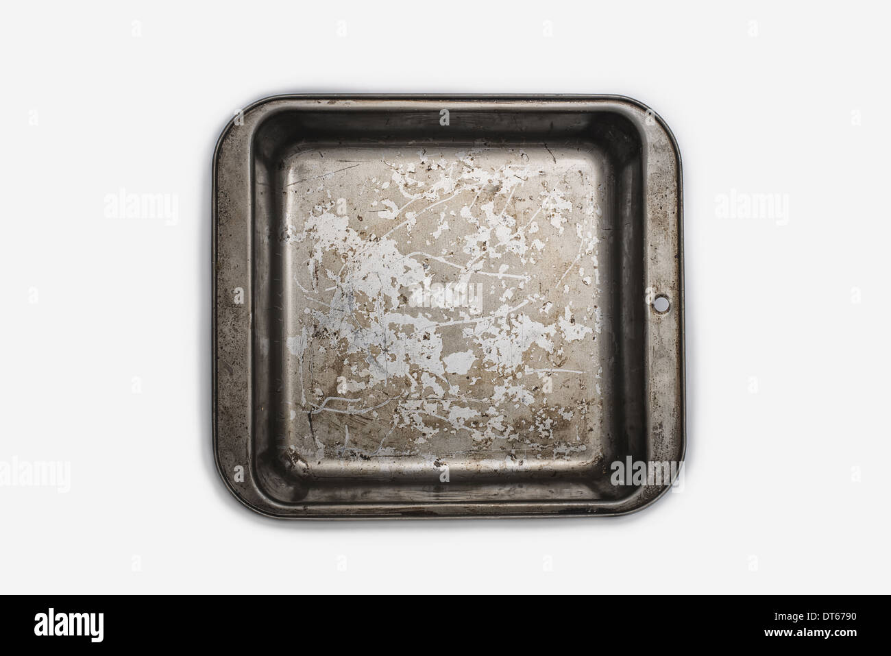A well used, seasoned baking tray. Cookware. A square baking cake tin 9 inches square. Pan. - Stock Image