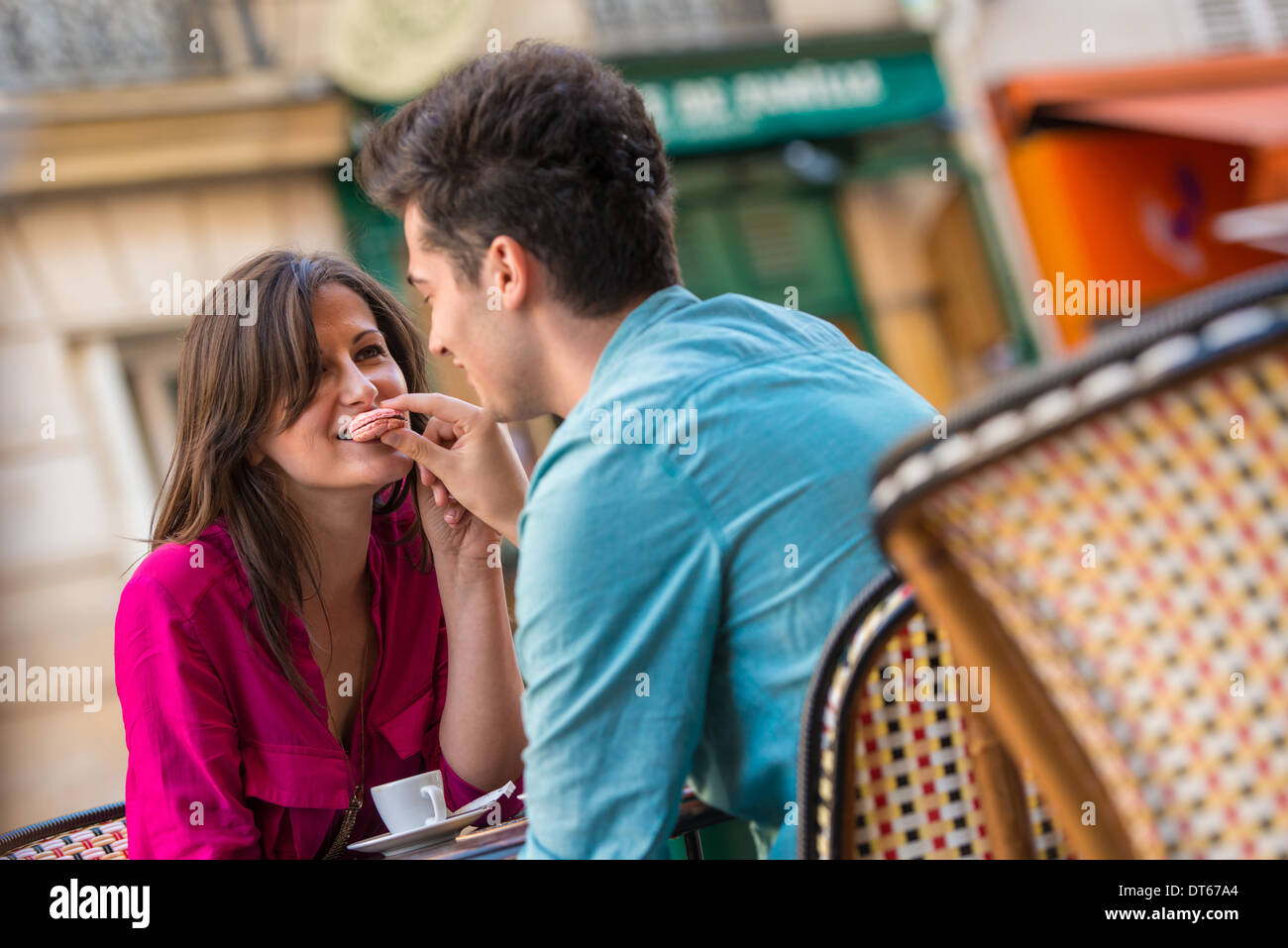 Young couple sharing macaroon at pavement cafe, Paris, France - Stock Image