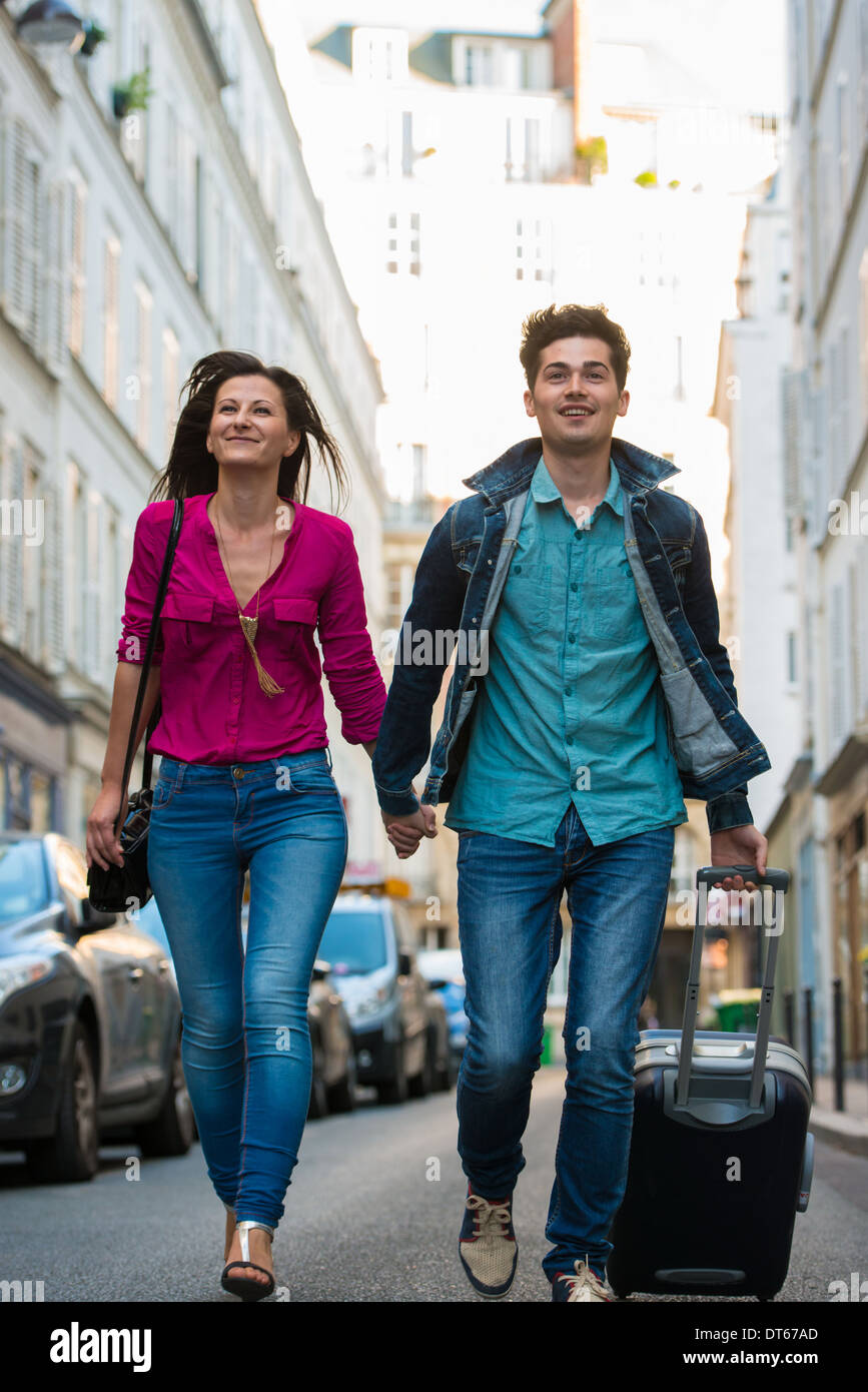 Young couple with wheeled suitcase, Paris, France - Stock Image
