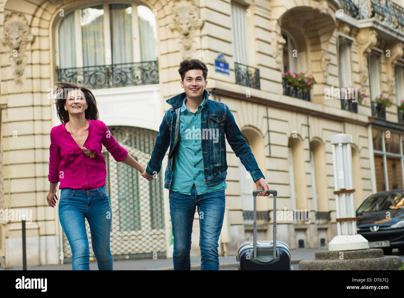 Young couple walking with wheeled suitcase, Paris, France - Stock Image