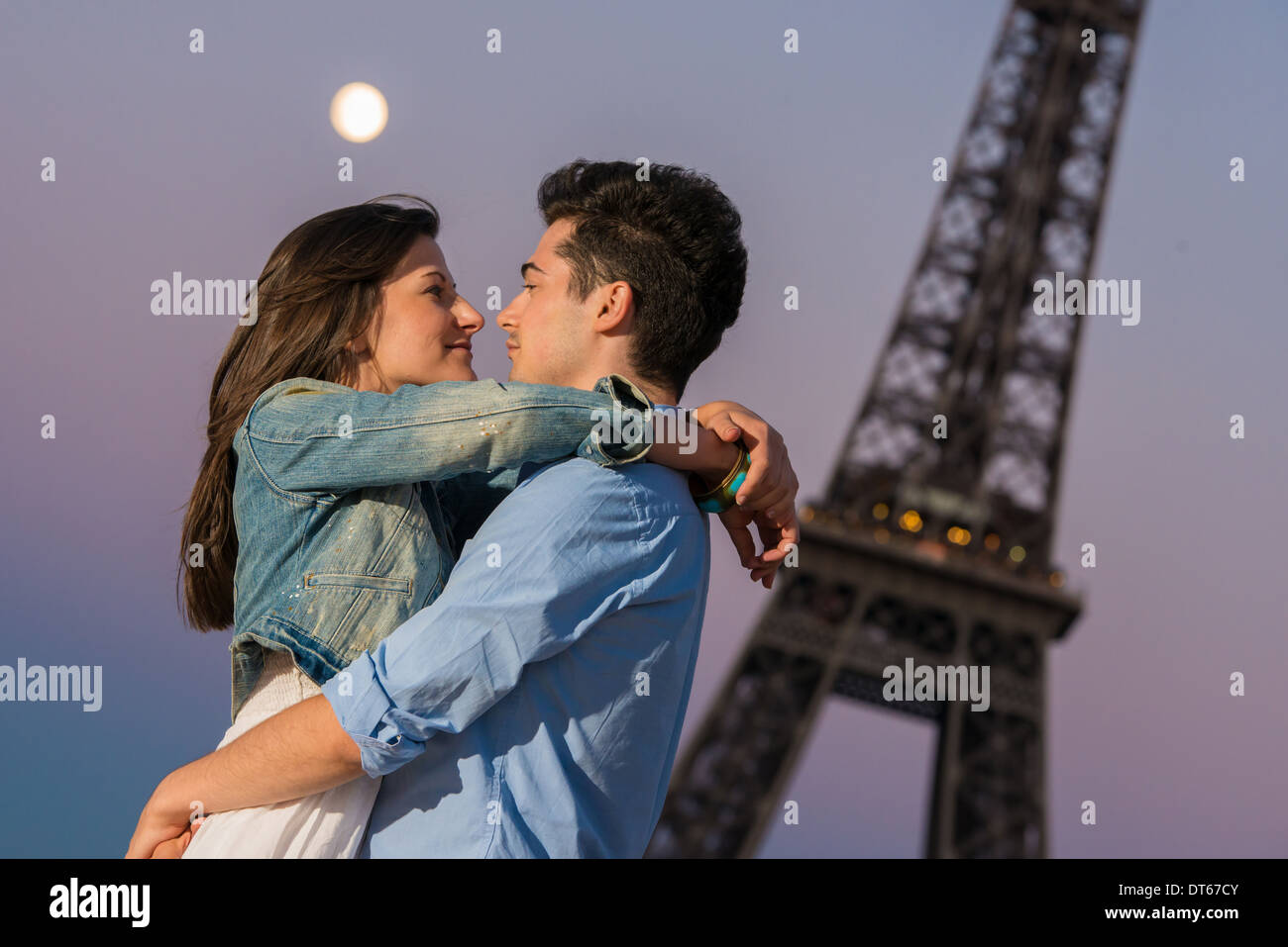 Young Couple Embracing In Moonlight Paris France