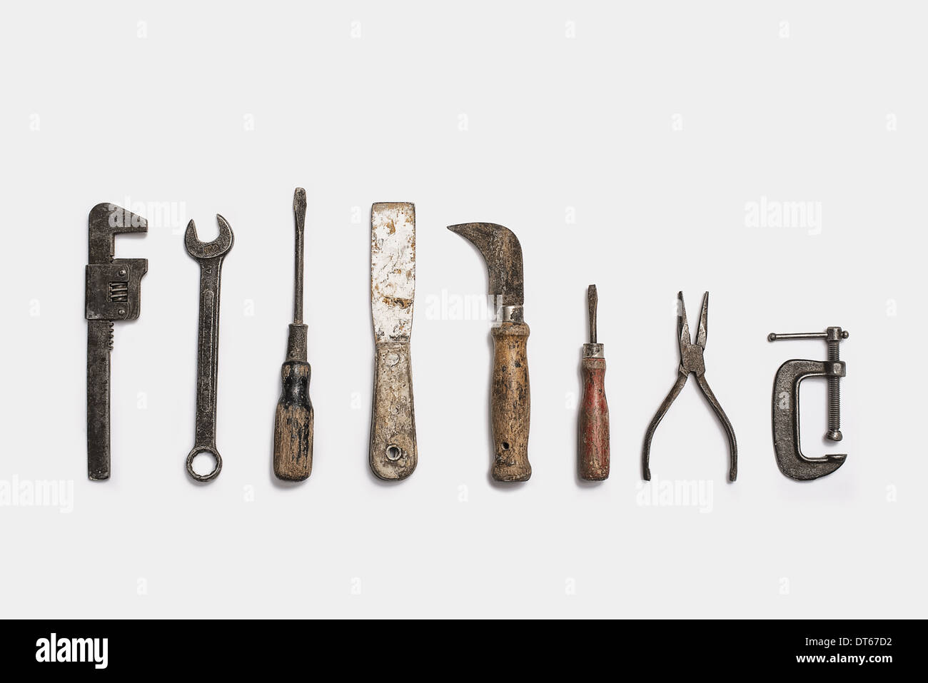Used tools arranged in a row. Well used, worn handles, shaped wooden smooth texture. Metal rusty and marked implements. - Stock Image