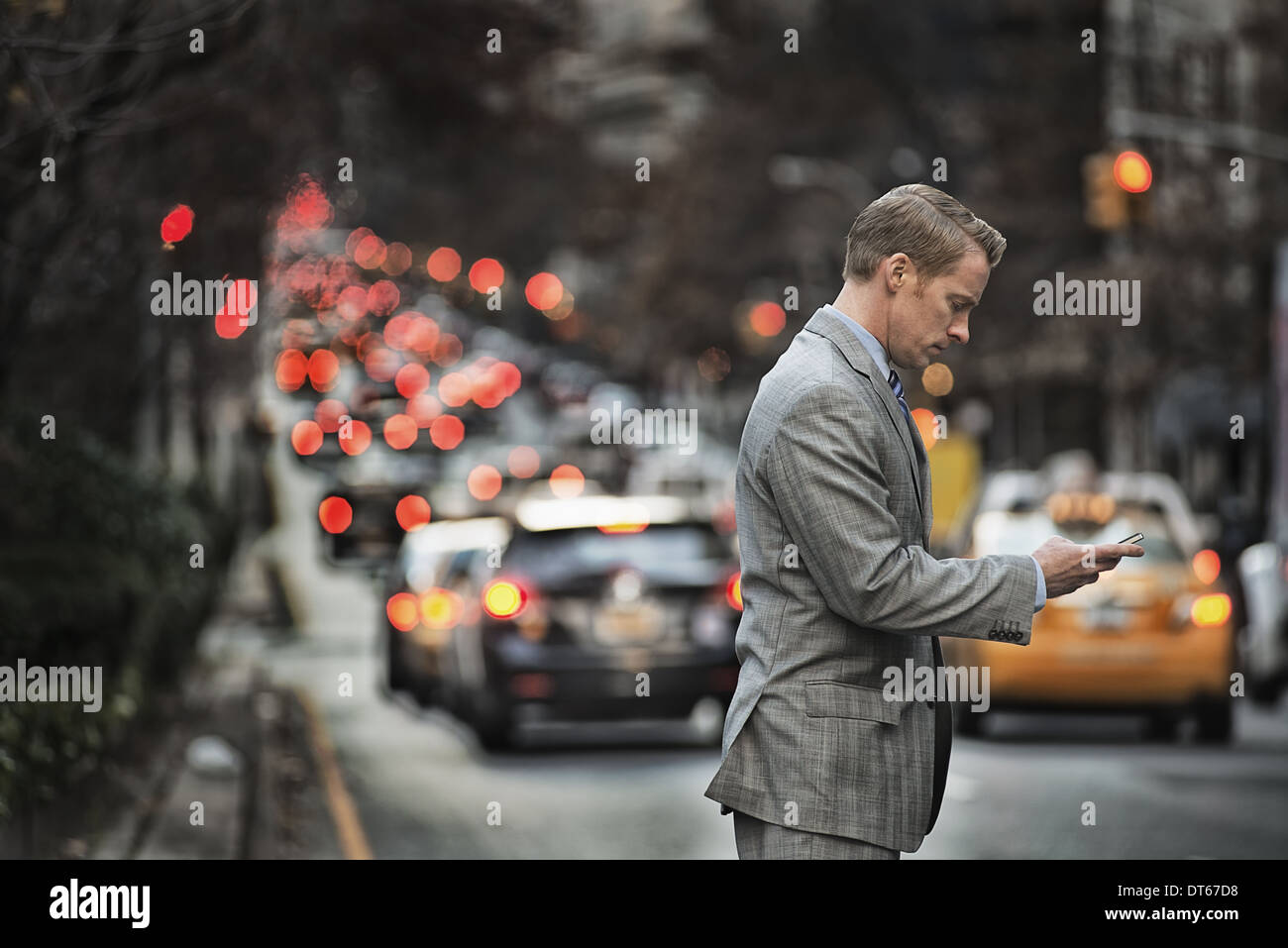 A man in a suit checking his cell phone, standing on a busy street at dusk. - Stock Image