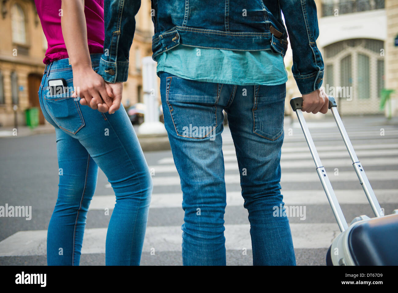 Young couple at crossing with wheeled suitcase, Paris, France - Stock Image