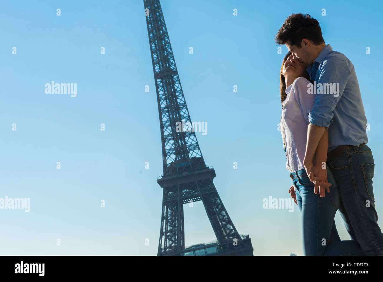Young couple embracing near Eiffel Tower, Paris, France Stock Photo