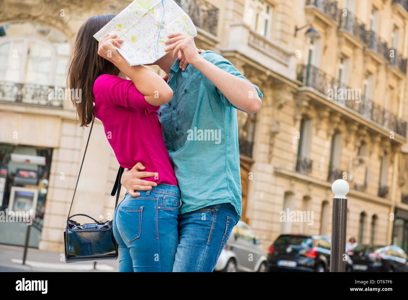 Young couple hiding behind map, Paris, France - Stock Image