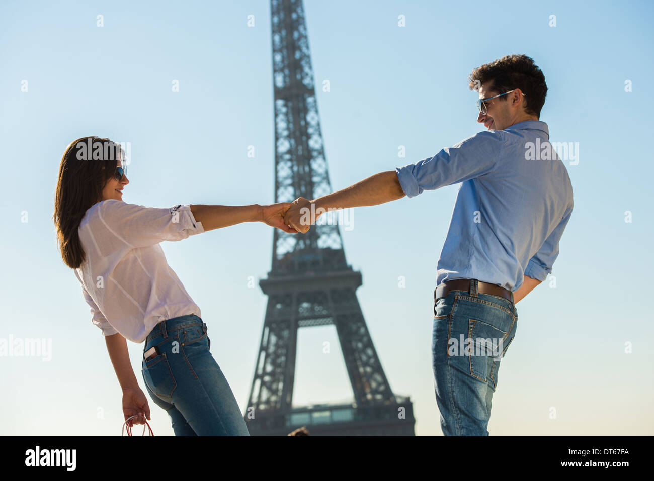 Young couple in front of Eiffel Tower, Paris, France - Stock Image