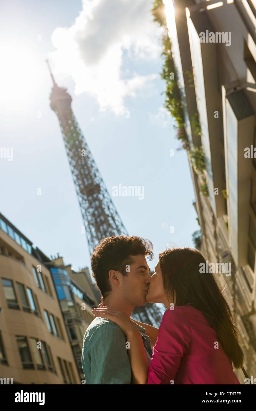 Young couple sharing a kiss in front of Eiffel Tower, Paris, France - Stock Image