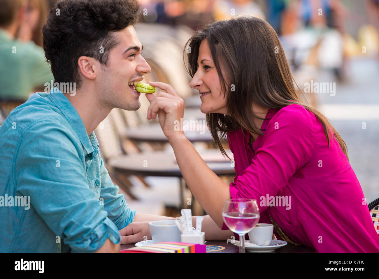 Young couple eating macaroon at pavement cafe, Paris, France - Stock Image
