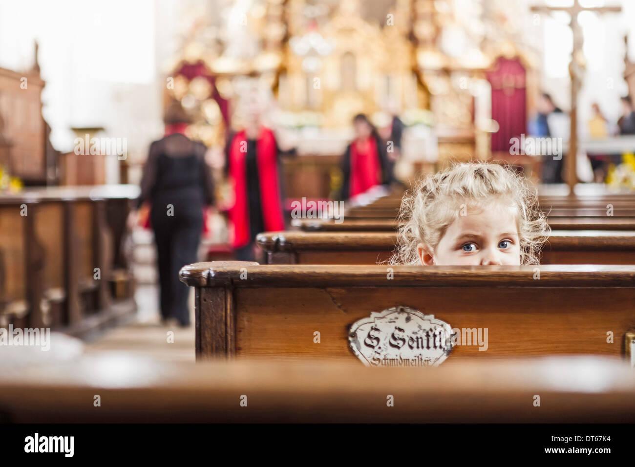 Portrait of female toddler peeking over church pew - Stock Image