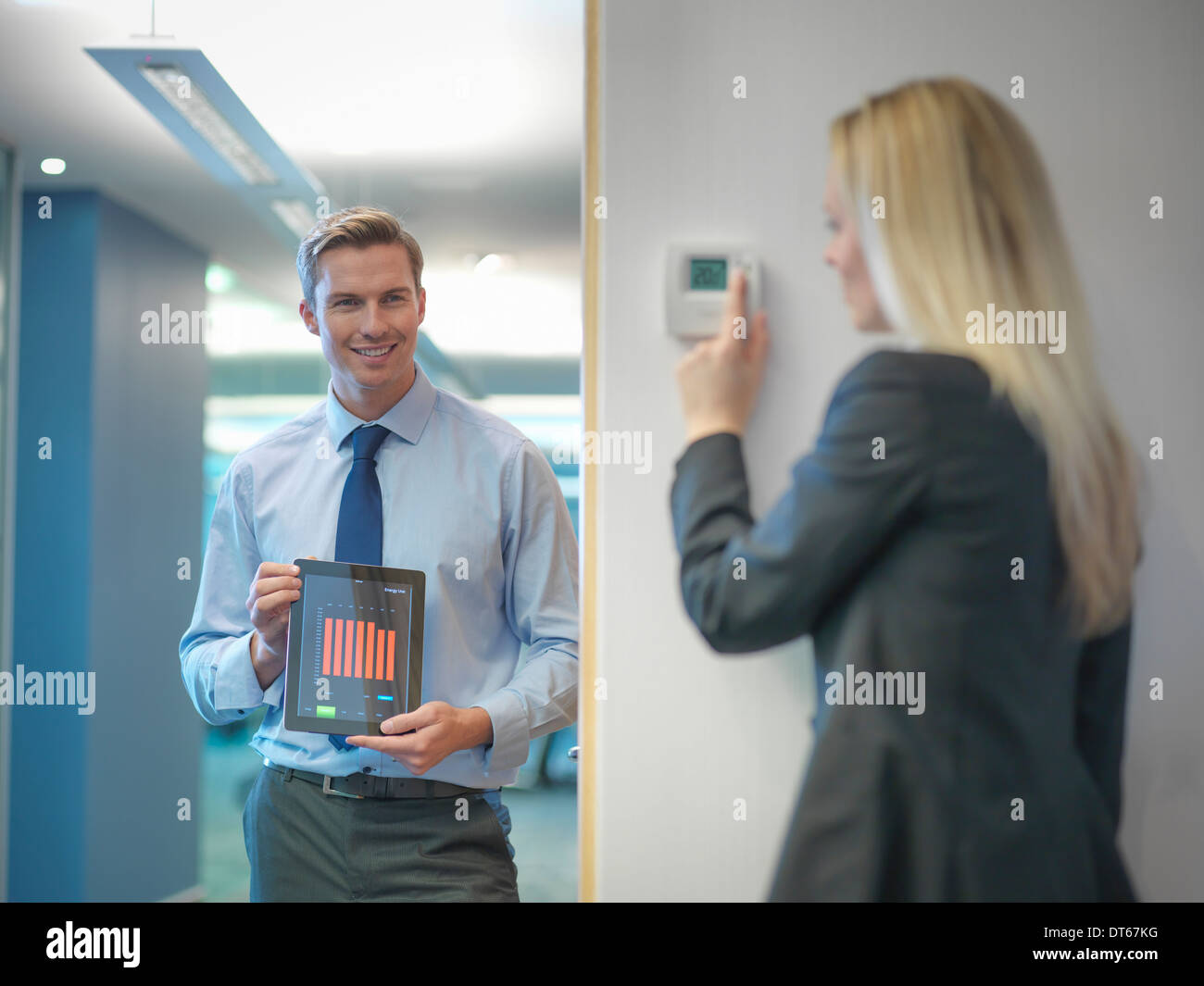 Office workers adjusting heating thermostat and recording information on digital tablet - Stock Image