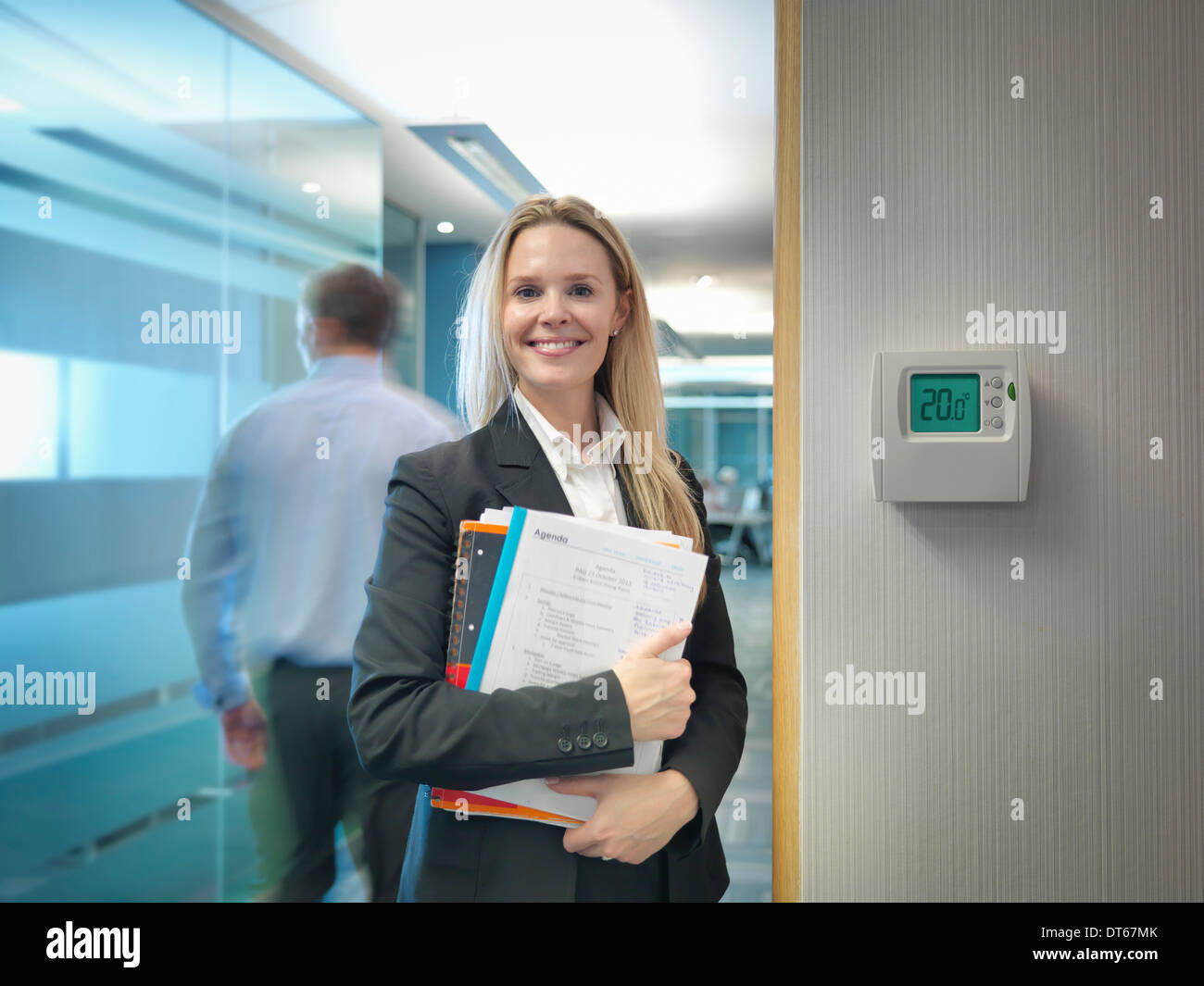 Portrait of office worker next to office thermostat adjusted to make energy savings - Stock Image