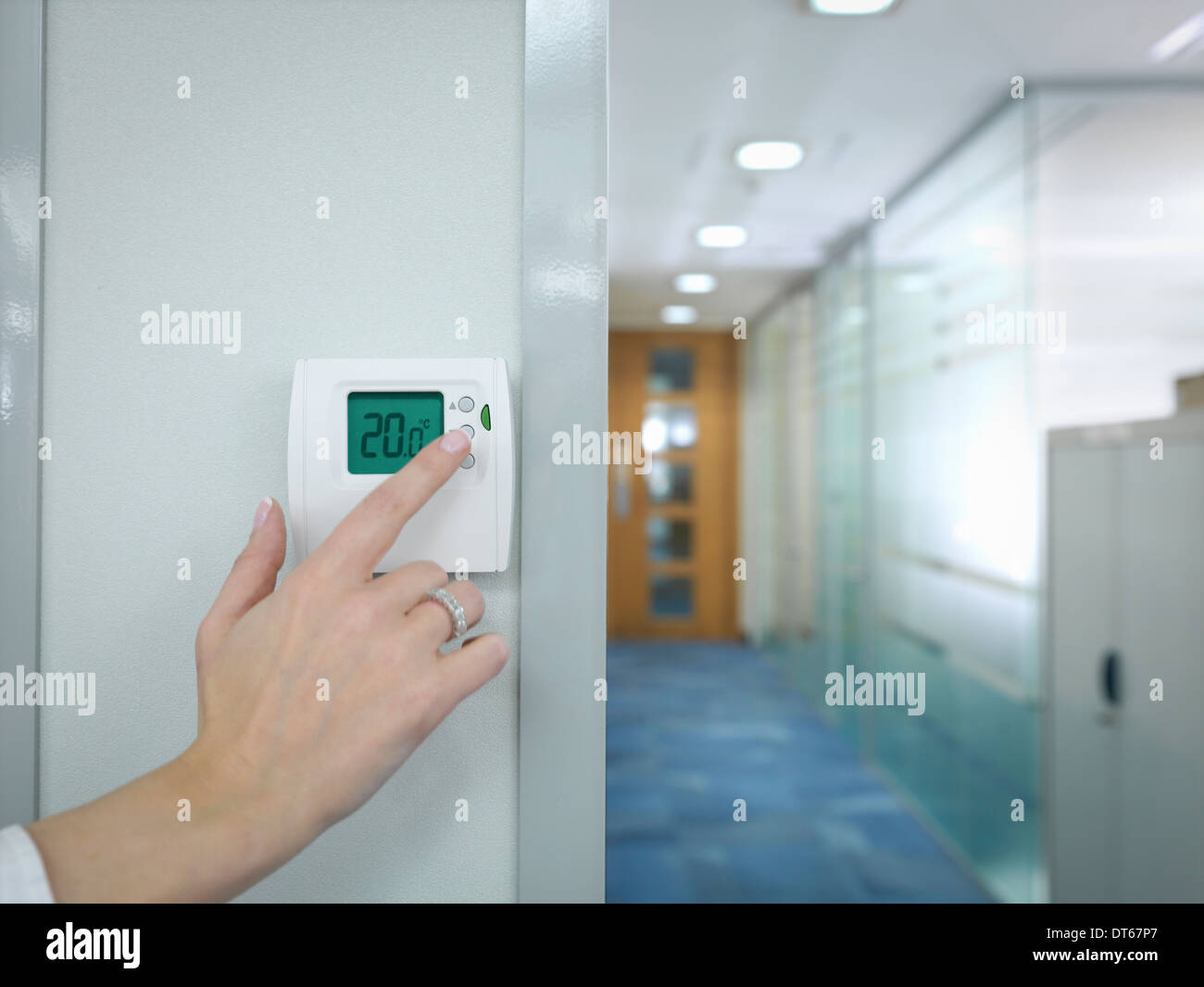 Close up of office worker adjusting thermostat - Stock Image