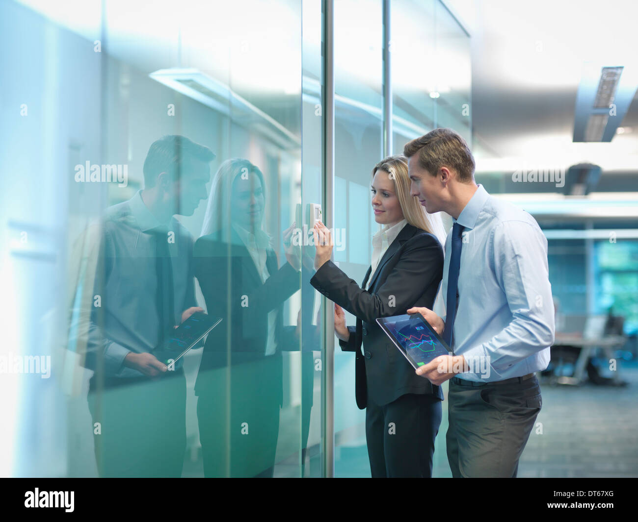 Office workers adjusting heating thermostat in modern workplace - Stock Image