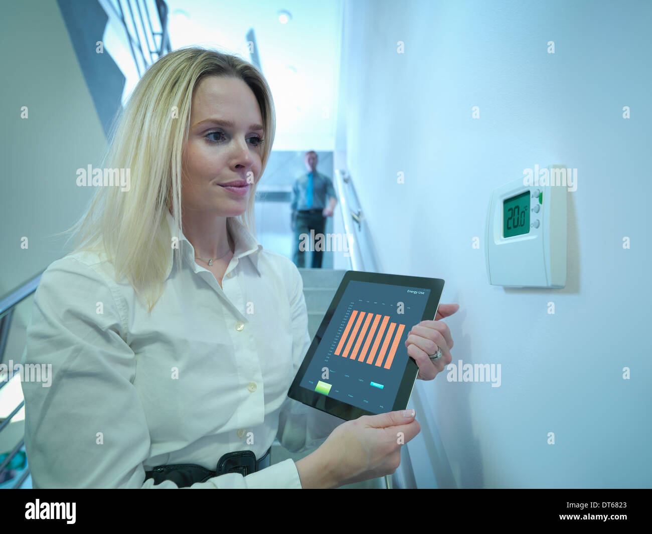 Office worker holding digital tablet next to office thermostat in stairwell - Stock Image