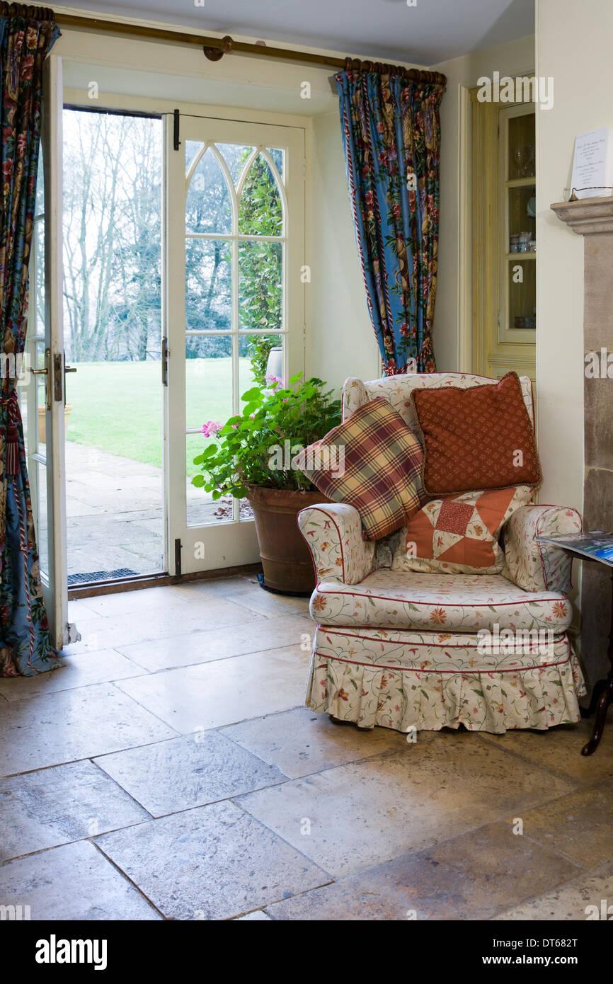 Cosy kitchen armchair by an open garden door. - Stock Image