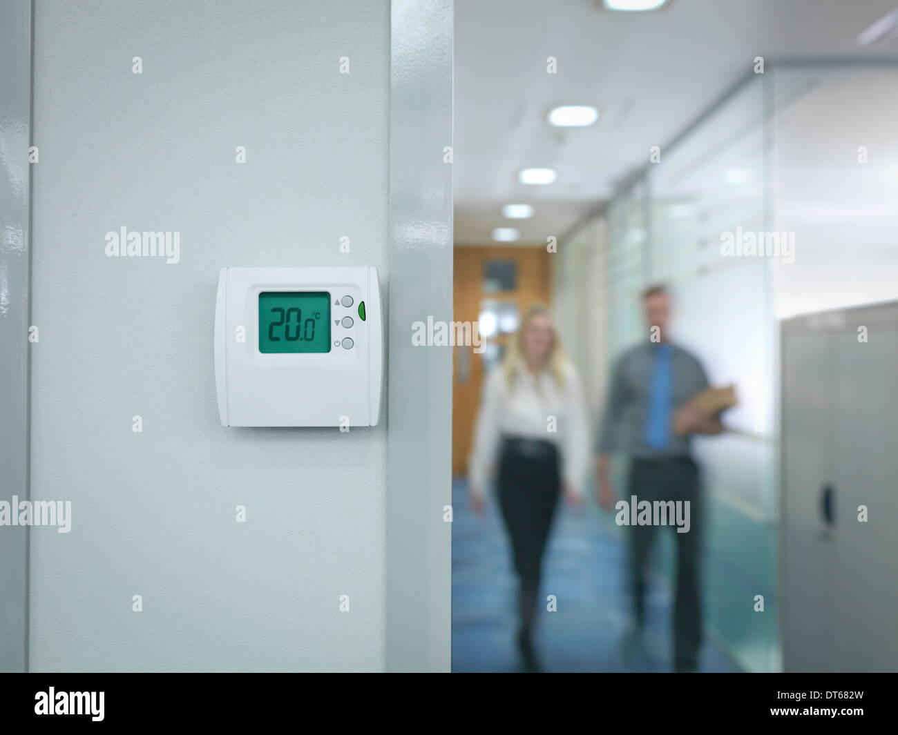 Office workers walking towards thermostat - Stock Image