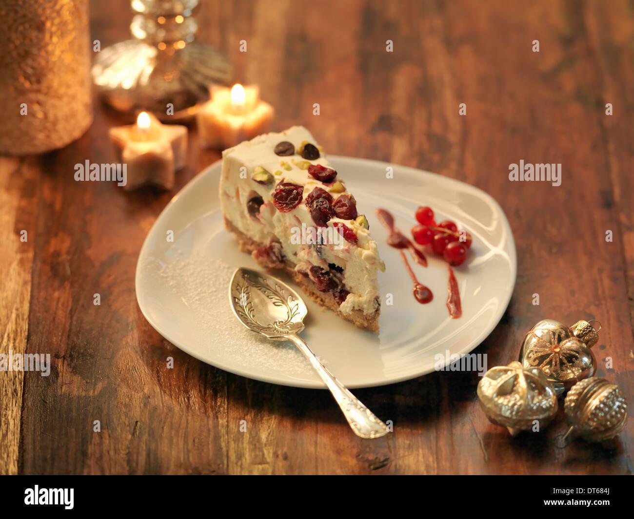 Mascarpone cheesecake with cranberry, pistachio, orange zest and chocolate chip amongst festive decorations - Stock Image
