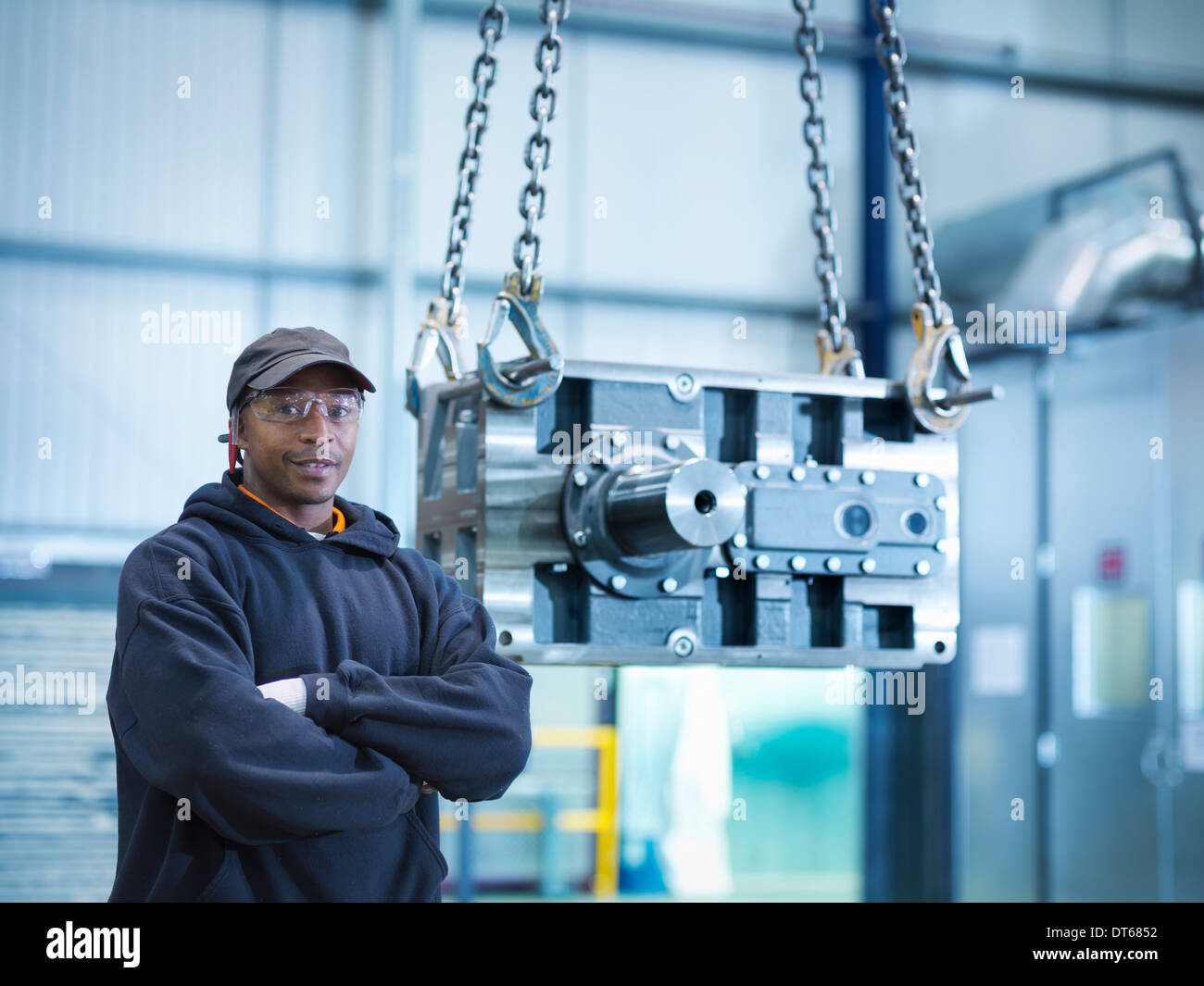 Engineer with industrial gearbox in engineering factory, portrait - Stock Image