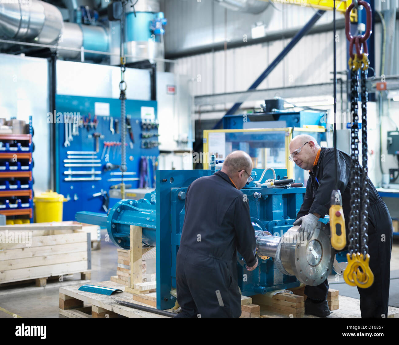 Mature engineers working in engineering factory - Stock Image